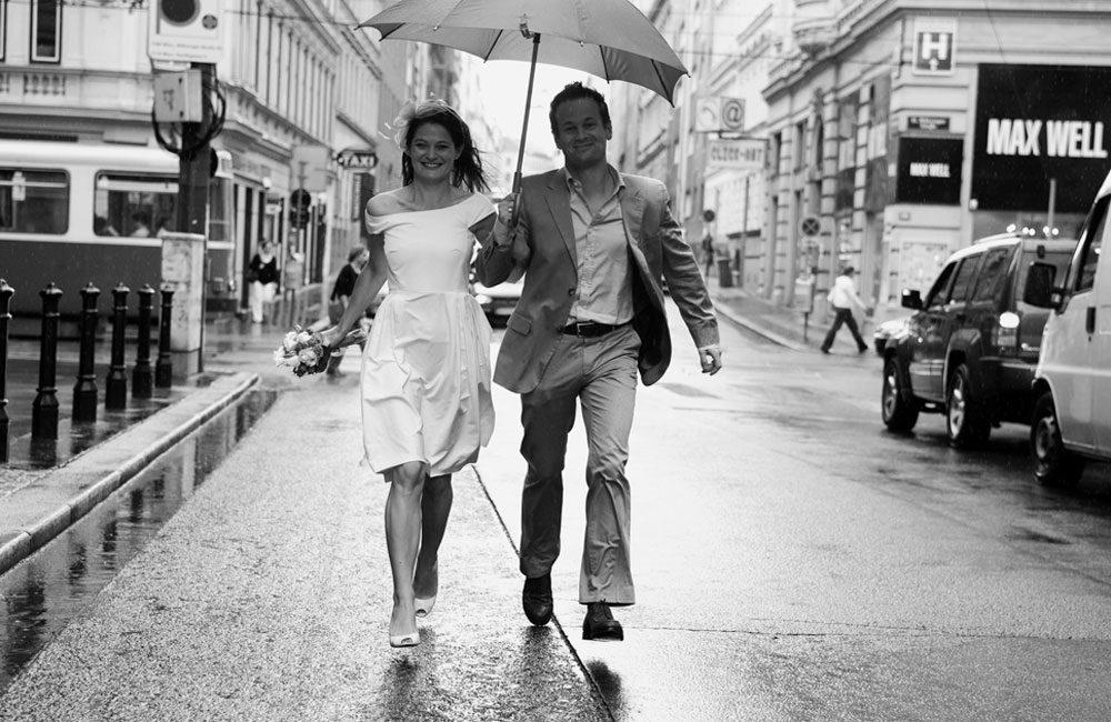 braut und bräutigam gehen im regen mit schirm claus scheucher hochzeitsfotograf